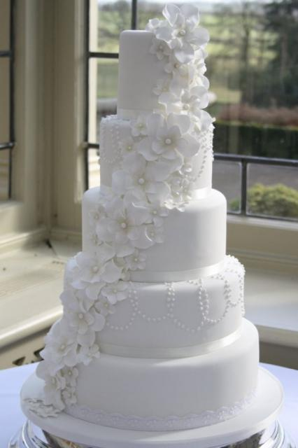 5 tier round white wedding cake with white flowers draping down, classic style