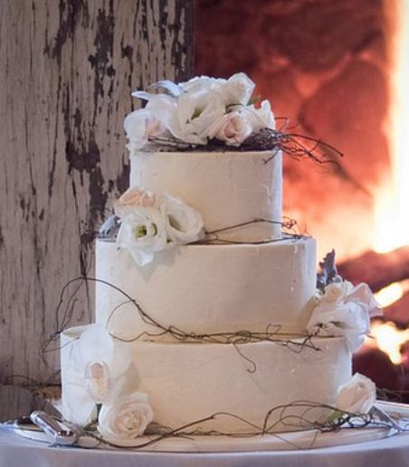 Classic with a twist, Tri-tier round white wedding cake with white roses and branches