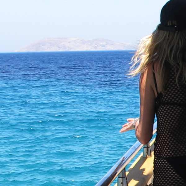 Serifos on a yacht wearing a black Prada bikini and an Isabel Marant fishnet top